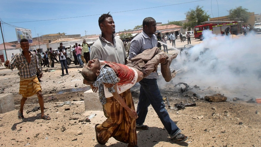 March 18, 2013 - Somali men carry a seriously wounded man after a car bomb blast close to the Somali government's headquarters in the capital Mogadishu, Somalia.