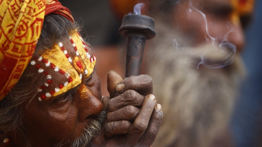 "A Hindu Holy man smokes marijuana  during the ""Shivaratri"" festival at the courtyard of the Pashupatinath temple in Katmandu, Nepal, Sunday, March 10, 2013. ""Shivaratri"", or the night of Shiva, is dedicated to the worship of Lord Shiva, the Hindu god of death and destruction.(AP Photo/Niranjan Shrestha)"