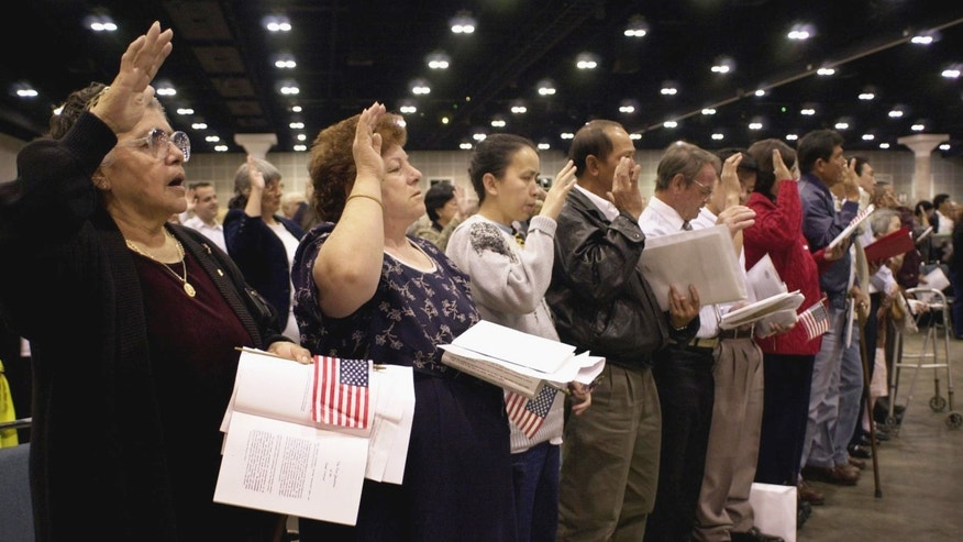Immigrants from such countries as Mexico, El Salvador, Vietnam, the Philippines and Iran raise their hands as they are sworn in as United States citizens.