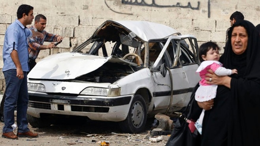 March 20, 2013: People inspect a damaged car at the scene of a car bomb attack in Zayona neighborhood of eastern Baghdad, Iraq. Iraqi officials say a car bomb in eastern Baghdad has killed and wounded a few people on the 10th anniversary of the US-led invasion, the day after a series of well-coordinated attacks left scores dead.