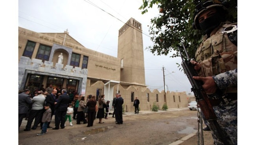 December 25, 2012: An Iraqi policeman stands guard outside the St. Joseph Chaldean church during a mass on Christmas in Baghdad.