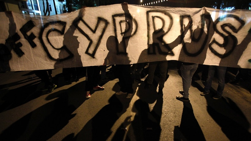 "March 24, 2013: Protesters hold a banner that reads ""Hands off Cyprus"" during an anti-bailout rally outside European Union house in capital Nicosia, Cyprus."
