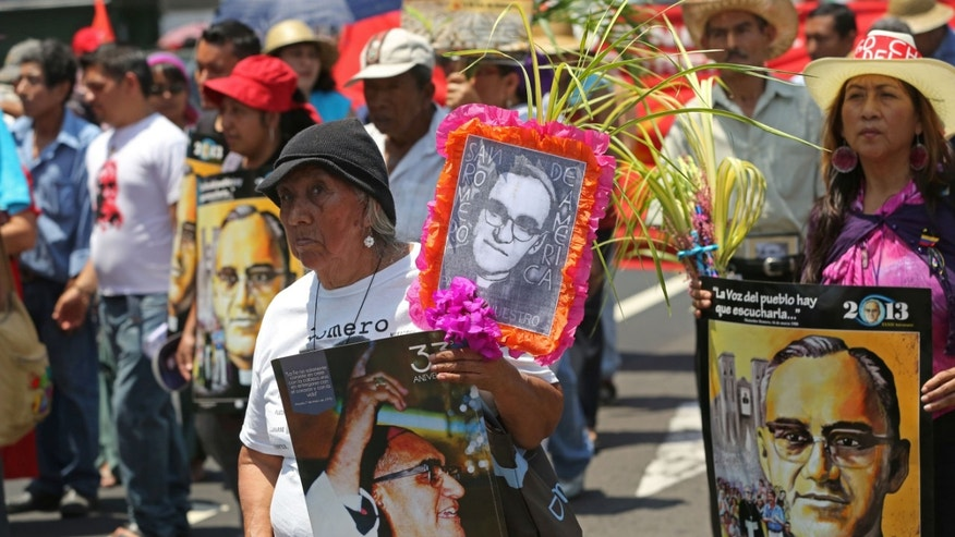 Salvadorans carry signs honoring martyred Archbishop Oscar Arnulfo Romero during a Palm Sunday march through the streets of San Salvador, El Salvador,  Sunday March 24, 2013.