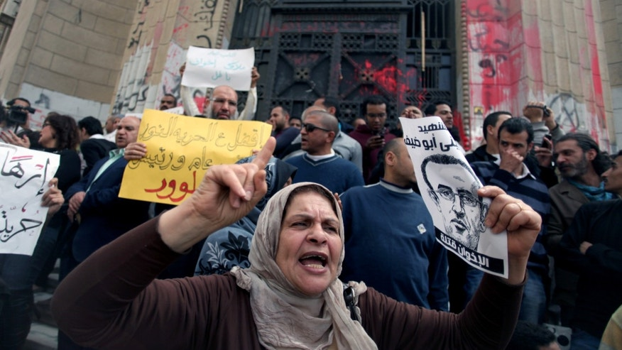 Protesters chant in front of the general prosecutor's office in Cairo this week after the arrest of a prominent blogger and four others following violent  clashes between supporters and opponents of the Muslim Brotherhood. (AP Photo/Khalil Hamra)