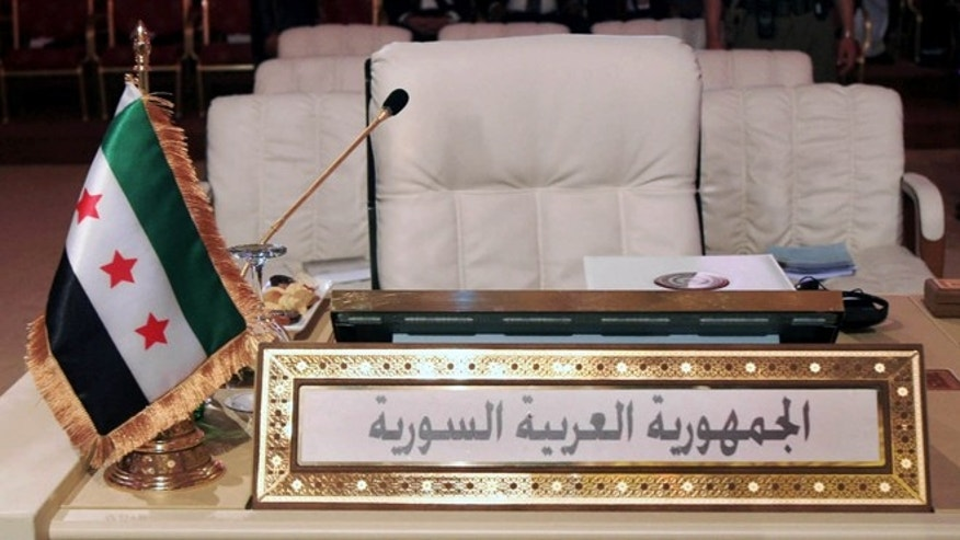 March 26, 2013: The Syrian revolutionary flag, is seen in front of the empty seat of the Syrian delegation during the opening session of the Arab League summit in Doha, Qatar. Syrian opposition representatives took the country's seat for the first time at an Arab League summit that opened in Qatar on Tuesday, a significant diplomatic boost for the forces fighting President Bashar Assad's regime.