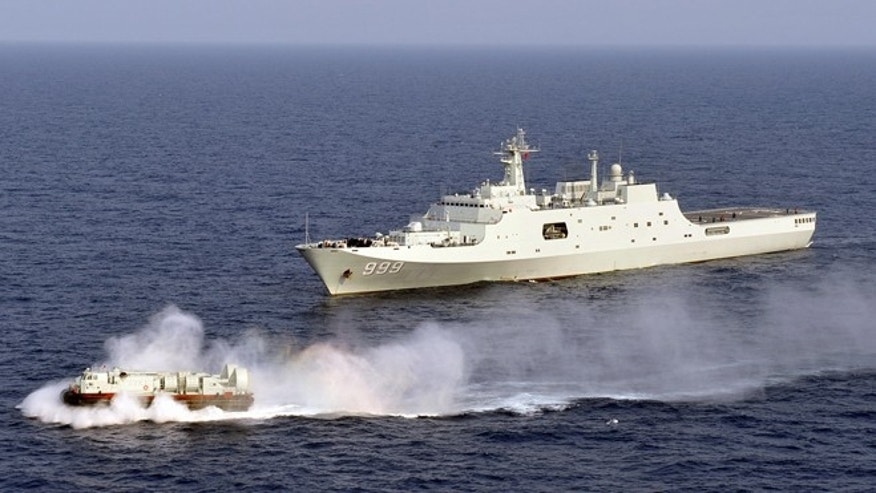 March 20, 2013: In this photo released by China's Xinhua News Agency, China's amphibious ship Jinggangshan is seen during a coordination training with a hovercraft in waters near south China's Hainan Province, in the South China Sea. Chinas increasingly powerful navy paid a symbolic visit to the countrys southernmost territorial claim deep in the South China Sea this week as part of military drills in the disputed Spratly Islands involving amphibious landings and aircraft. Sailors joined in the ceremony Tuesday, March 26 aboard Jinggangshan at James Shoal, a collection of submerged rocks, located 50 miles off the coast of Malaysia and about 1,120 miles from the Chinese mainland, the official Xinhua News Agency reported.
