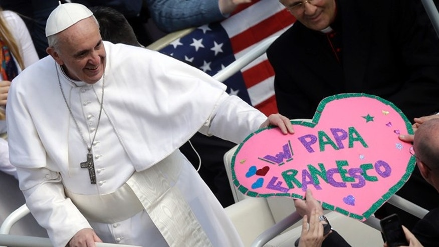 "Pope Francis is given a paper cut-out heart with writing reading ""Hurray Pope Francis"" as he driven through the crowd during his general audience, in St. Peter's Square, at the Vatican, Wednesday, March 27, 2013. Francis has called for an end to the violence and looting that has accompanied the weekend coup in the Central African Republic in his first such appeal for peace since becoming pope. (AP Photo/Gregorio Borgia)"
