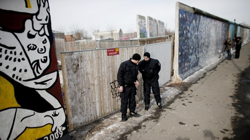 March 27, 2013: Police officers guard a construction site and sections of the East Side Gallery, while parts of the former Berlin Wall are removed in Berlin, Germany. Work crews backed by about 250 police have removed portions of the Berlin Wall known as the East Side Gallery to make way for an upscale building project, despite demands by protesters that the site be preserved.  Plans to remove part of the 3/4-mile stretch of wall sparked protests that developers were sacrificing history for profit.
