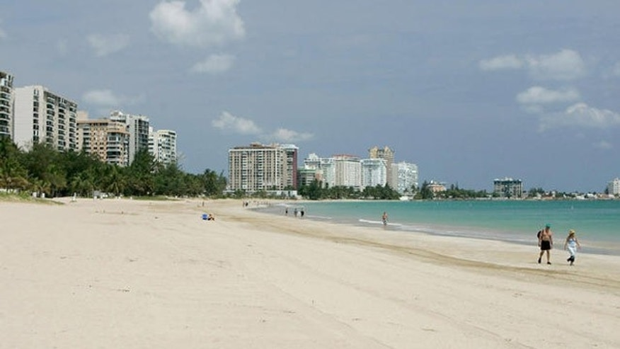 ** FILE **A couple of foreign tourists walk at Isla Verde Beach in San Juan, Puerto Rico in this June 11, 2007 file photo. The turquoise waters and white-sand beaches of the Caribbean appear to be losing some of their allure for U.S. tourists. Americans who flocked to the islands in record numbers until recently are finding new destinations or staying home, leading to declines of more than 10 percent this year in islands including Jamaica, St. Lucia and Grenada. (AP Photo/Andres Leighton)