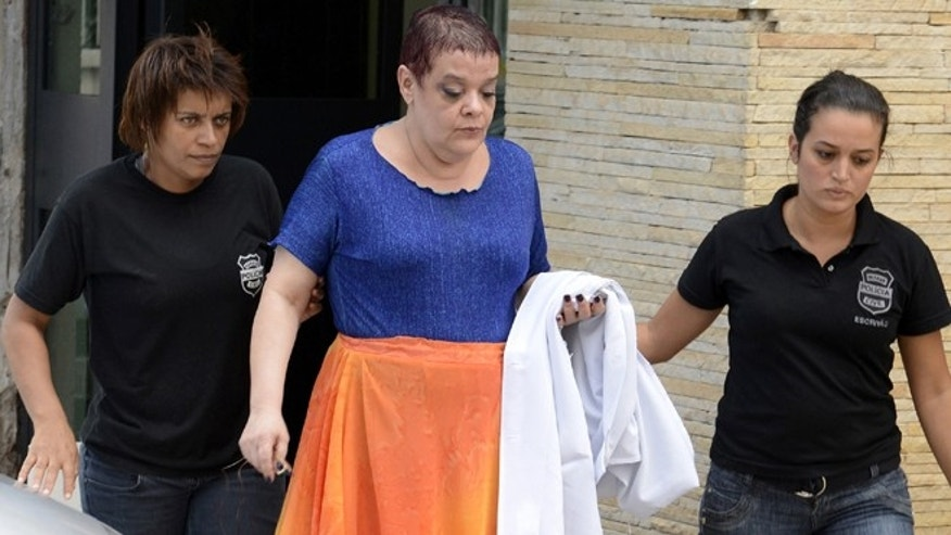 "Feb. 19, 2013: In this photo, Virginia Helena Soares de Souza, center, is escorted by police officers to a temporary prison in Curitiba, Parana state, Brazil. According to Brazil's health ministry, Soares de Souza, who's a medical doctor, and seven assistants are suspected of killing seven terminally ill patients in a southern Brazilian hospital, injecting them with ""drug cocktails"" and of tampering with their respirators."