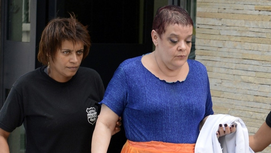 "In this Feb. 19, 2013 photo, Virginia Helena Soares de Souza, center, is escorted by police officers to a temporary prison in Curitiba, Parana state, Brazil. According to Brazil's health ministry, Soares de Souza, who's a medical doctor, and seven assistants are suspected of killing seven terminally ill patients in a southern Brazilian hospital, injecting them with ""drug cocktails"" and of tampering with their respirators. (AP Photo/Henry Milleo, Gazeta do Povo, Agencia O Dia)"