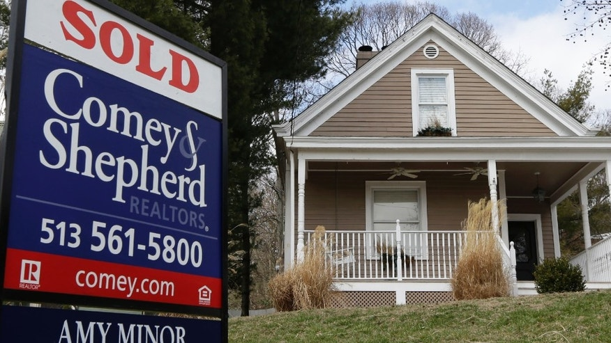 In this, Tuesday, March 12, 2013, photo, a sold sign is posted in front of a home for sale in Mariemont, Ohio. Average U.S. rates on fixed mortgages edged up this week but remained near historic lows. Low rates have helped drive the housing marketâs steady recovery.  (AP Photo/Al Behrman)