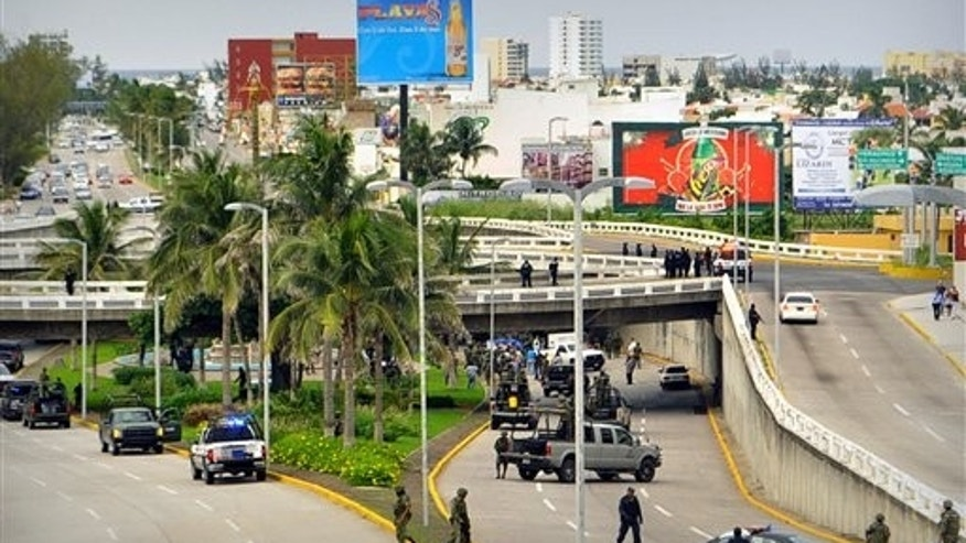 Sept 20: Soldiers and police block off an area where 35 bodies lie under an overpass in Veracruz, Mexico. Masked gunmen blocked traffic and left the bodies piled in two trucks and on the ground, according to authorities. The nation is now dominated by two powerful organizations that appear poised for a one-on-one battle to control drug markets and trafficking routes. (AP Photo)