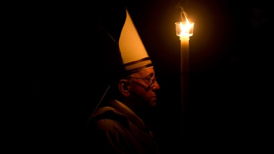 March 30, 2013: Pope Francis holding a tall, lit, white candle, enters a darkened St. Peter&#39&#x3b;s Basilica, at the Vatican to begin the Vatican&#39&#x3b;s Easter vigil service.