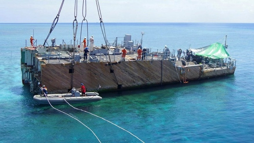 March 29, 2013: In this photo released by the Philippine Coast Guard, workers prepare for lifting of a part of the dismantled hull of the USS Guardian on the Tubbataha Reef, a World Heritage Site in southwest of the Philippines. Workers in the southwestern Philippines have removed the last major part of a U.S. Navy minesweeper from a protected coral reef where it ran aground in January, and the damage will be assessed to determine the fine Washington will pay, officials said Sunday, March 31, 2013.