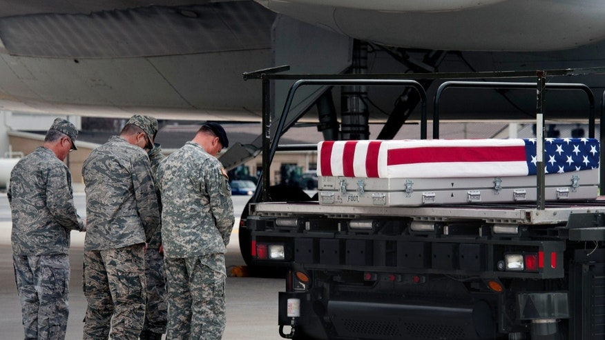 March 28, 2013 -  U.S. Army and Air Force officers say a prayer beside the transfer case containing the remains of Army Sgt. Michael Cable, 26, of Philpot, Kentucky, to a transfer vehicle at Dover Air Force Base, Delaware.