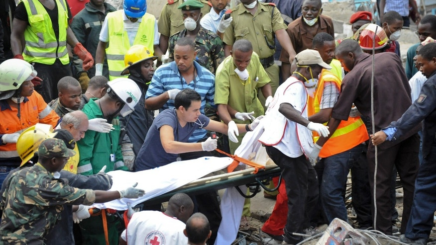 Mar. 29, 2013: Rescuers from the Tanzania Red Cross carry away a body from the rubble of a collapsed building in downtown Dar es Salaam, Tanzania.