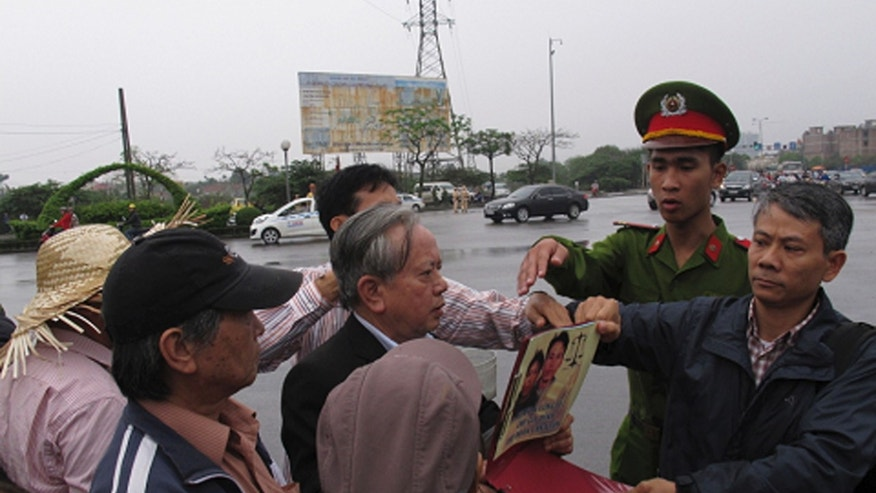 A Vietnamese police officer tries to take away a poster from a protestor outside a court in Haiphong, Vietnam, Tuesday, April 2, 2013. A Vietnamese court begun hearing the trial of four fish farmers charged with attempted murder for fighting back against police and army officers seeking to evict them from their land last year. (AP Photo/Chris Brummitt)