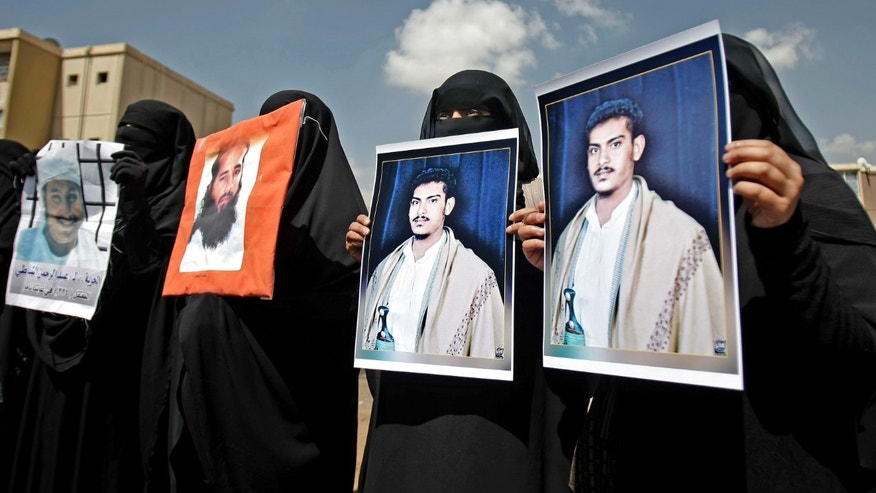 April 1, 2013 - Yemeni women hold photos of their relatives detained in Guantanamo Bay prison during a demonstration in front of the U.S. embassy demanding their release, in Sanaa, Yemen.