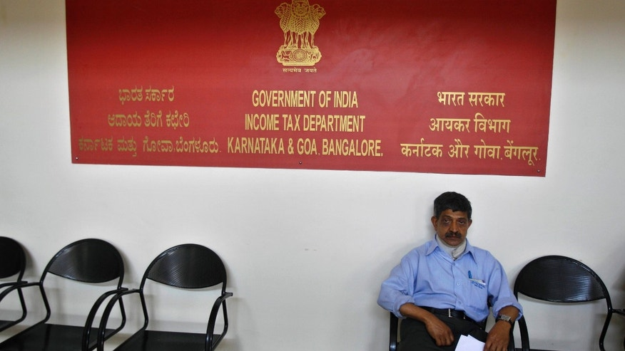 In this Monday, March 25, 2013 photo, an Indian taxpayer waits outside a help center set up for salaried employees and pensioners at an Income Tax office in Bangalore, India. In a country of 1.2 billion people, a country where years of staggering economic growth have created tens of thousands of new millionaires annually and a recent slowdown has done little damage to a thriving luxury goods market, far less than .01 percent of the population admits they are in the top tax bracket. Less than 3 percent of Indians file income tax returns at all, and officials say only about 1.5 million taxpayers declare earning more than 1,000,000 rupees per year (about $18,000). (AP Photo/Aijaz Rahi)
