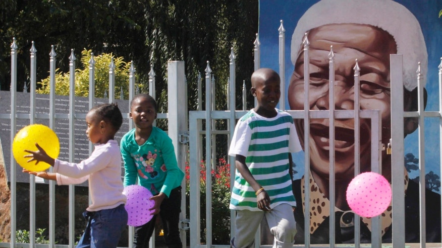 Children play ball in front of a giant portrait of former president Nelson Mandela in a park in Soweto, South Africa, Sunday, March 31, 2013. Mandela remains in a hospital while he receives treatment for a recurrence of pneumonia. Presidential spokesman Mac Maharaj says there are no updates on 94 year old Mandela since an official statement Saturday on his condition. That statement reported the anti-apartheid leader was breathing without difficulty after having a procedure to clear fluid in his lung area. (AP Photo/Denis Farrell)