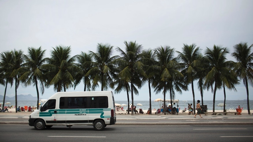 A public transport van picks up passengers along Copacabana beach in Rio de Janeiro, Brazil, Tuesday, April 2, 2013.  An American woman was gang raped and beaten aboard a public transport van while her French boyfriend was shackled, hit with a crowbar and forced to watch the attacks after the pair boarded the vehicle in Rio de Janeiro's showcase Copacabana beach neighborhood, police said.  The attacks took place over six hours starting shortly after midnight on Saturday. (AP Photo/Felipe Dana)