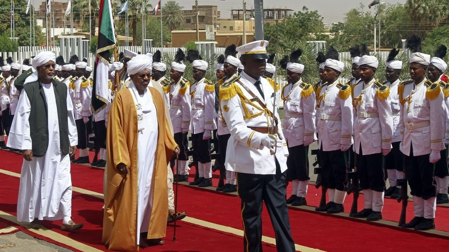 In this Monday, April,1, 2013 photo, Sudanese President Omar al-Bashir reviews an honor guard as he arrives to address  Parliament in Khartoum. Sudanese officials say the government has released seven political prisoners, including a female politician, under an amnesty declared by al-Bashir. An unspecified number of politicians, and military and intelligence officers remain in jail accused of plotting to overthrow al-Bashir, who seized power in a military coup in 1989. (AP Photo/Abd Raouf)