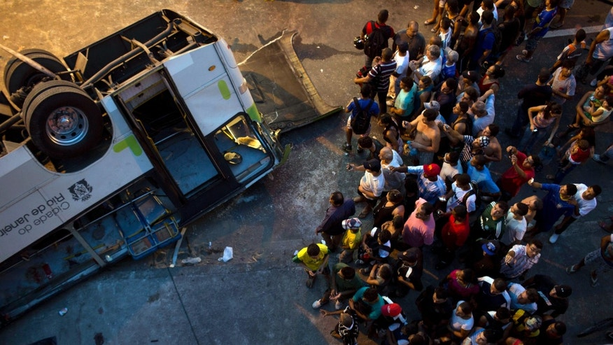 People watch a bus that fell from a viaduct into Avenida Brasil, the largest avenue in Rio de Janeiro, Brazil, Tuesday, April 2, 2013. A passenger bus plunged from a 10-meter-high (30-foot) viaduct in central Rio de Janeiro killing at least seven people and closing a major thoroughfare. (AP Photo/Felipe Dana)