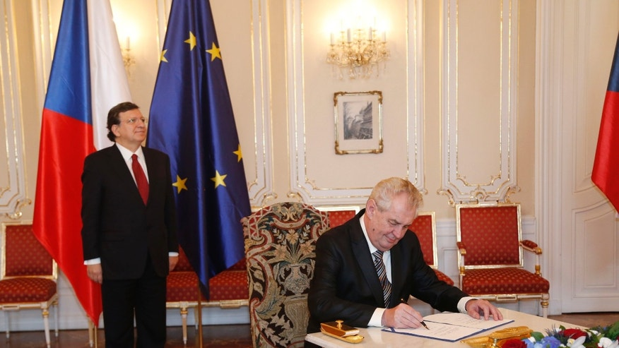 European Commission President Jose Manuel Barroso, left, looks on as Czech Republic's President Milos Zeman, right, signs the European Union bailout fund at the Prague Castle in Prague, Czech Republic, Wednesday, April 3, 2013. (AP Photo/Petr David Josek)