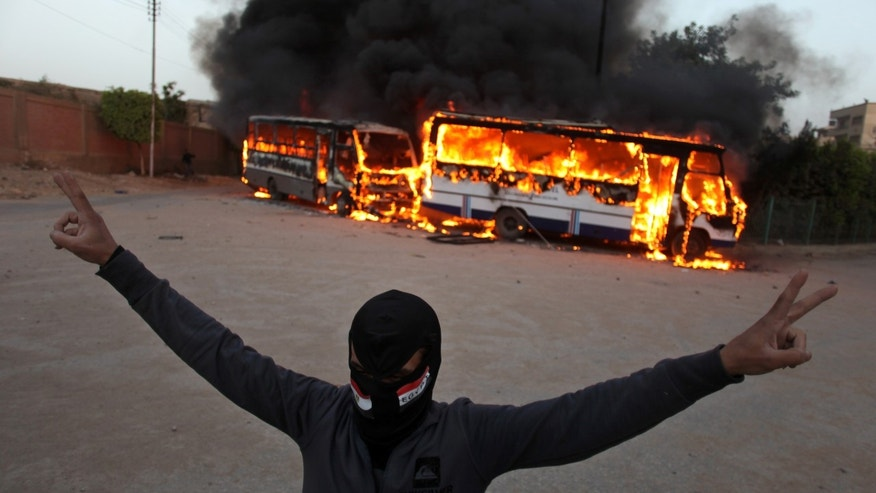 "FILE - In this Friday, March 22, 2013 file photo, a masked protester flashes the victory sign as he stands in front of burning buses during clashes between supporters and opponents of Egypt's powerful Muslim Brotherhood near the Islamist group's headquarters in Cairo, Egypt. Known as the ""Battle of the Mountain,"" a ferocious recent fight between members of Egypt's Muslim Brotherhood and their opponents in Cairo is looking like a dangerous turning point in the country's political turmoil. Some protesters showed a new willingness to turn to violence against Islamists they accuse of dominating Egypt, while Islamists have heightened their calls for action against opponents they accuse of trying to topple the president. (AP Photo/Khalil Hamra, File)"