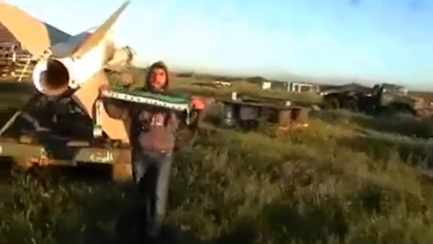 This image taken from video obtained from Ugarit News, which has been authenticated based on its contents and other AP reporting, shows a man holding a scarf in the colors of the Syrian revolutionary flag after rebels seized a military base in Daraa, Syria, on Wednesday, April 3, 2013. Syrian rebels captured a military base in the country's south on Wednesday after days of heavy fighting, activists said, in the latest advance by opposition fighters near the strategic border area with Jordan. (AP Photo/Ugarit News via AP video)