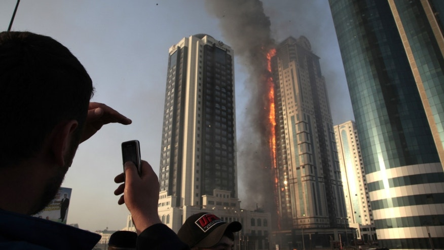 A local resident makes photos with a mobile phone of a fire in a high-rise apartment building in provincial capital Grozny, Russia, Wednesday, April 3, 2013. French actor Gerard Depardieu reportedly received an apartment in the complex of buildings as a gift from Chechen leader Ramzan Kadyrov. (AP Photo/Musa Sadulayev)