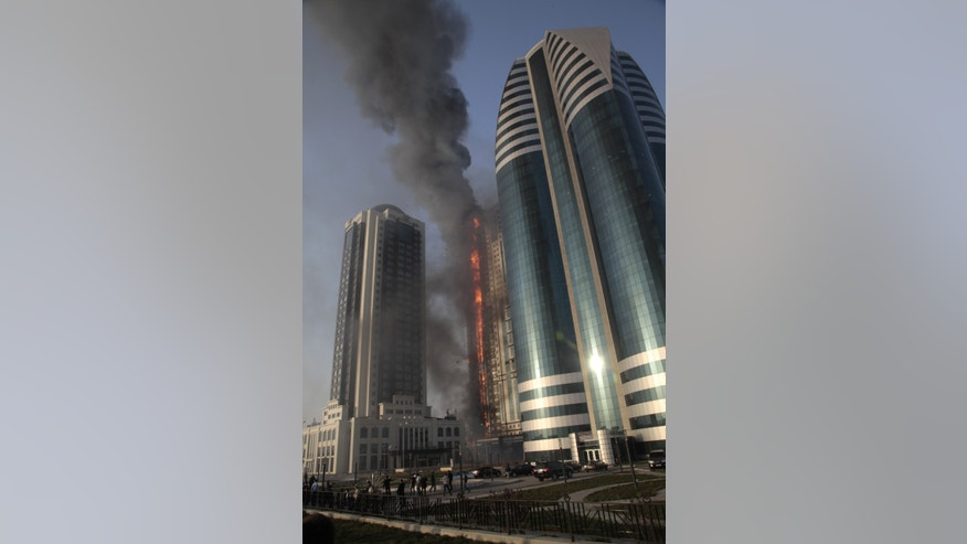 A fire rages in a high-rise apartment building in provincial capital Grozny, Russia, Wednesday, April 3, 2013. French actor Gerard Depardieu reportedly received an apartment in the complex of buildings as a gift from Chechen leader Ramzan Kadyrov. People are not living in the building yet. ( AP Photo/Musa Sadulayev)