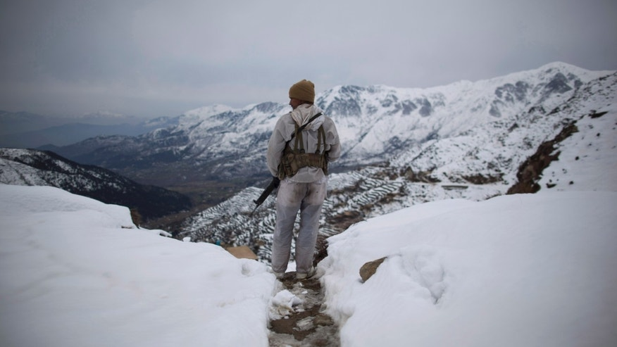 FILE-This Feb 17, 2012 file photo shows a Pakistani Army soldier with the 20th Lancers Armored Regiment, standing atop the 8000 foot mountain during a patrol near his outpost Kalpani Base in Pakistan's Dir province on the Pakistan-Afghan border. Relations between the two countries have not been good in recent years, with Afghanistan often blaming Pakistan for supporting insurgents that are fighting both NATO troops and government forces. Major attacks and suicide bombings are regularly blamed on Pakistan, playing to a domestic audience that increasingly considers its neighbor responsible for the war. (AP Photo/Anja Niedringhaus, File)