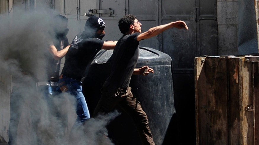 April 2, 2013: Palestinians throw stones at Israeli soldiers after the death of Maysara Abu Hamdiyeh in Israeli jail in the West Bank city of Hebron.