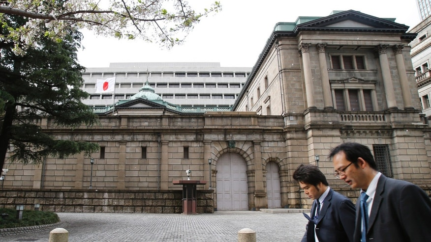 People walk in front of the Bank of Japan building in Tokyo Thursday, April 4, 2013. Japan is making a drastic shift in monetary policy in its latest attempt to spur inflation and get the world's third-largest economy out of a long, debilitating slump. (AP Photo/Koji Sasahara)