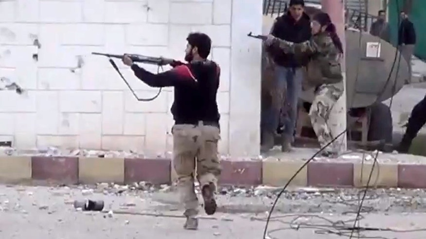 In this Monday March 18, 2013 file image taken from video obtained from the Shaam News Network, which has been authenticated based on its contents and other AP reporting, shows free Syrian Army fighters fire at Syrian army soldiers during a fierce firefight in Daraa al-Balad, Syria.
