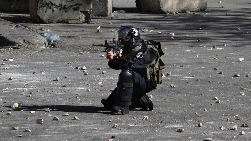 April 4, 2013: An Israeli Border Police officer aims towards Palestinian protesters, not pictured, during clashes in the West Bank city of Hebron.