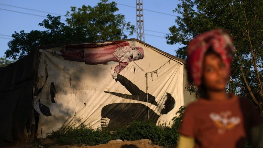 A Pakistani girl, right, walks by a tent covered with a banner showing cricket legend-turned politician Imran Khan, in a Christian slum on the outskirts of Islamabad, Pakistan, Friday, April 5, 2013. Pakistani officials have provoked both laughter and criticism in recent days as they vetted potential candidates in the country's upcoming national elections with questions that veered between the controversial and the bizarre. (AP Photo/Muhammed Muheisen)