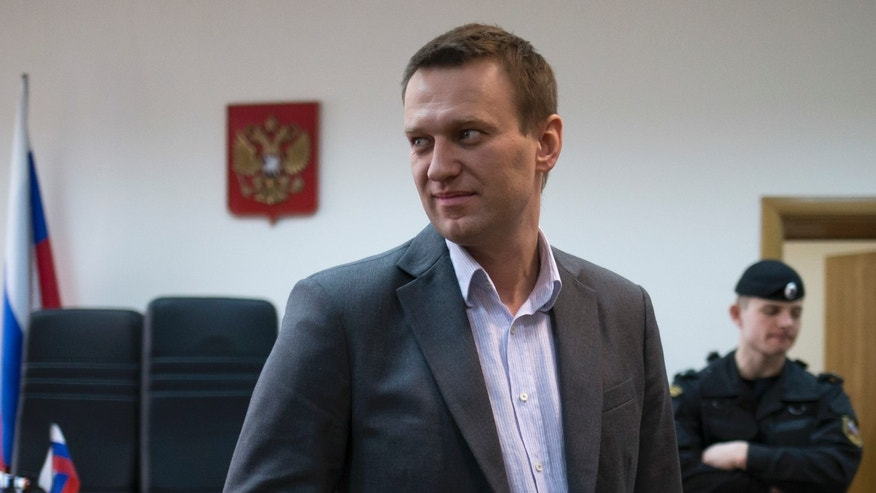 In this photo taken on Wednesday, March 13, 2013, Russian opposition activist Alexey Navalny talks to journalists inside a courtroom in Moscow, Russia. Navalny, a prominent Russian opposition leader says he plans to contest the country's presidential election slated for 2018, and would prosecute President Vladimir Putin if he wins. Navalny, a charismatic 36-year old lawyer, made his name exposing official corruption before spearheading a series of massive protests in Moscow against Putin's return to the presidency in the March 2012 vote for another six-year term. (AP Photo/Alexander Zemlianichenko)