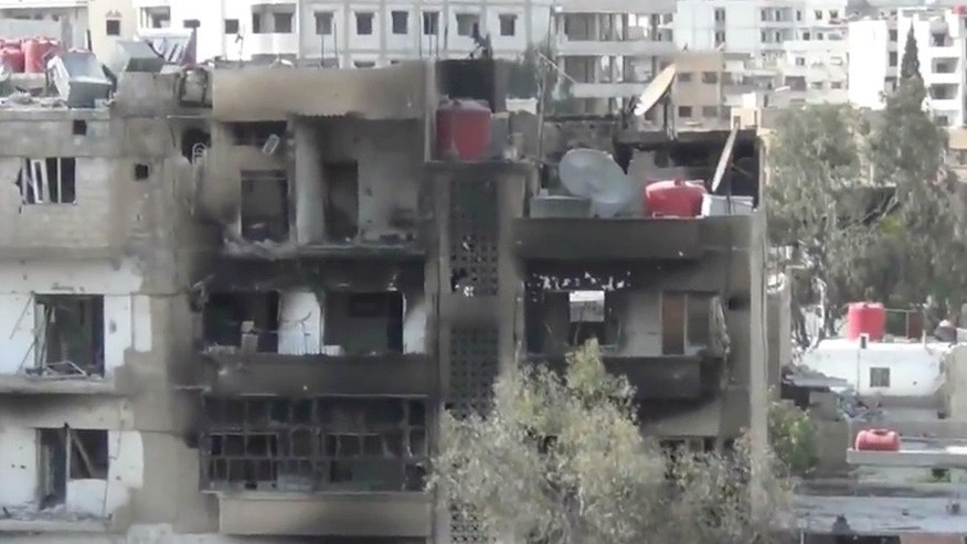 This image taken from video obtained from the Shaam News Network, which has been authenticated based on its contents and other AP reporting, shows a damaged building due to heavy shelling in the Damascus suburb of Daraya, Syria, on Wednesday, April 3, 2013. (AP Photo/Shaam News Network via AP video)