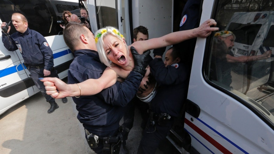 April 4, 2013 - Police officers detain an activist from the women's rights group Femen as she takes part in a protest in Paris.