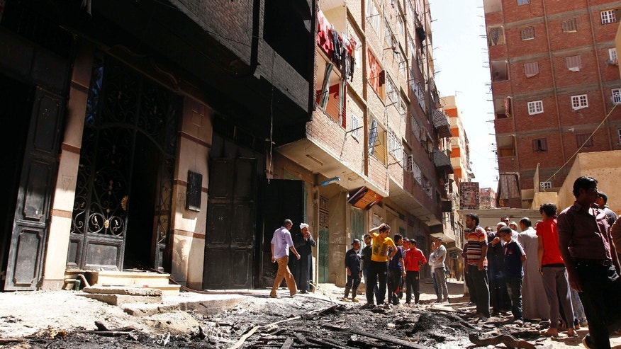 April 6, 2013: Onlookers gather at the house of Egyptian Christian, Samir Iskandar which was burned during clashes between Muslims and Christians in Qalubiya, just outside Cairo, Egypt.