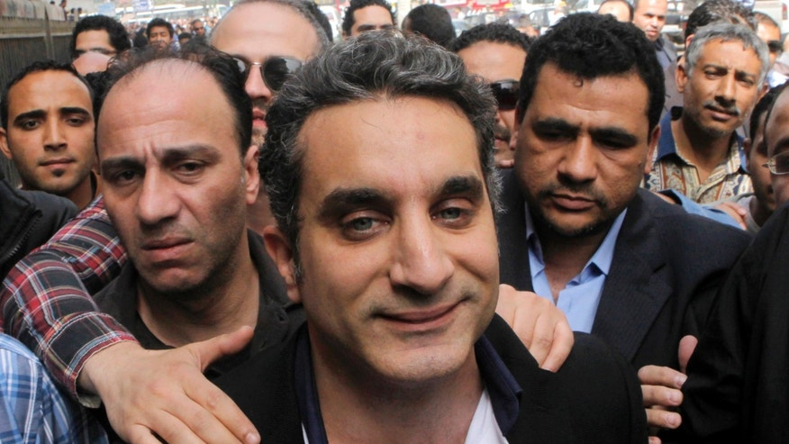 March 31, 2013: In this file photo, a bodyguard secures popular Egyptian television satirist Bassem Youssef, who has come to be known as Egypt's Jon Stewart, as he enters Egypt's state prosecutors office to face accusations of insulting Islam and the country's Islamist leader in Cairo, Egypt.