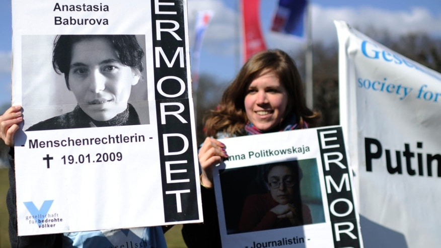Demonstrators  protest with posters of  journalists Anastasia Baburova killed in 2009, left, and of  Anna Politkovskaya killed in 2006, outside the Congress centrum in Hannover, were German chancellor Angela Merkel and Russian President Vladimir Putin are expected to meet and  to  deliver speeches at the Hannover Industrial Fair  Sunday April 7, 2013. Words at right on the posters read : Killed.  (AP Photo/dpa,Alexander Koerner)