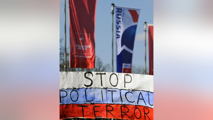 Protest banners are placed outside the Congress Center in Hannover, Germany to demonstrate against the Russian government Sunday April 7, 2013. German chancellor Angela Merkel and Russian President Vladimir Putin are expected to meet  there  this evening. (AP Photo/dpa  Alexander Koerner)