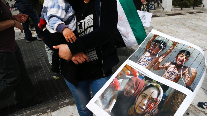 Syrians who now live in Greece, display photos of injured people in Syria, during a  protest against Syrian President Bashar Assad , in front of the Greek Parliament, in Athens, Saturday April 6, 2013. Around 200 Syrians took part in the protest.  (AP Photo/Dimitri Messinis)