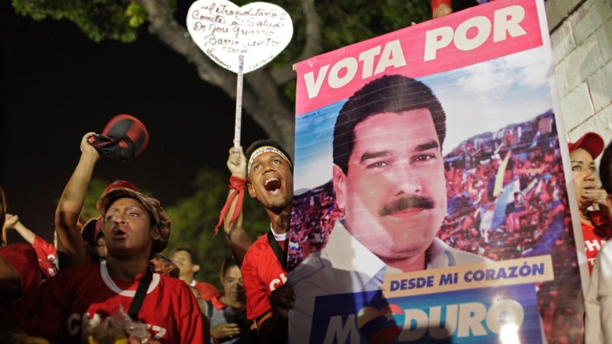 Supporters of Venezuela's interim President Nicolas Maduro cheer during campaig rally in Caracas, Venezuela, Friday, April 5, 2013. The presidential election to replace Venezuela's late President Hugo Chavez is scheduled for April 14. (AP Photo/Ariana Cubillos)