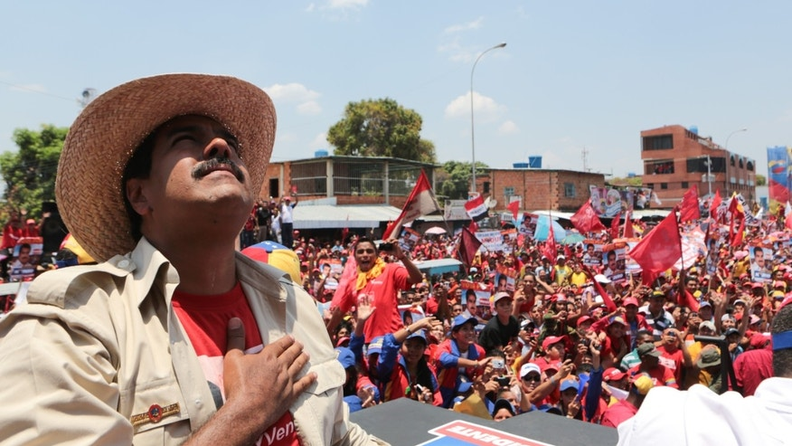 In this photo released by Miraflores Press Office, Venezuela's acting President Nicolas Maduro looks up during a campaign rally in San Fernando de Apure, Venezuela, Sunday, April 7, 2013. Maduro is running againt opossition candidate Henrique Capriles to replace Venezuela's late President Hugo Chavez on April 14. (AP Photo/Miraflores Press Office/Marcelo Garcia)