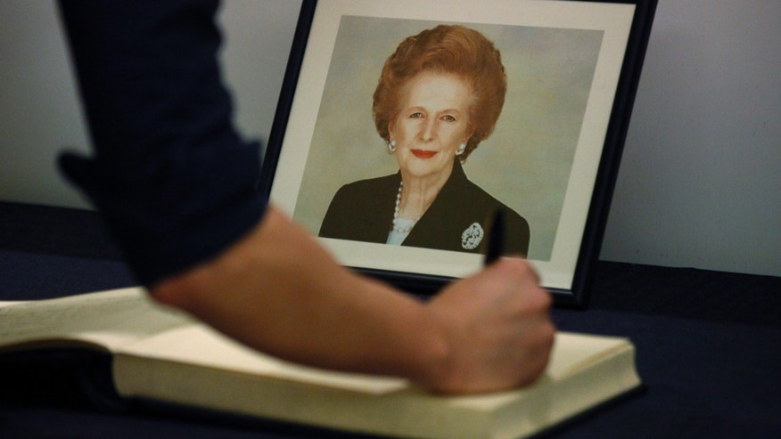 A man signs the condolence book in front of a  picture of former British Prime Minister Margaret Thatcher at the British Consulate in Hong Kong Tuesday, April. 9, 2013.